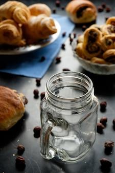 Pusty słoik na herbatę na czarnym stole wśród herbatników i rogalików