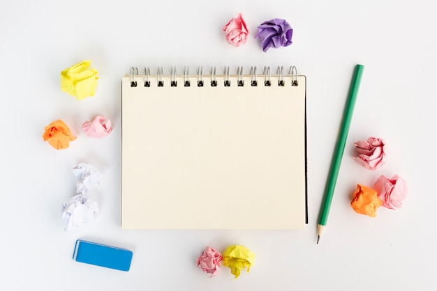 Pusty spiralny pamiętnik otoczony zmiętym papierem z ołówkiem i gumką