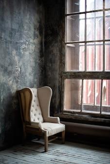 Pusty staromodny fotel przy oknie