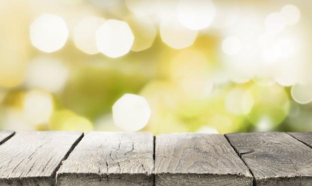 Pusty stary drewniany blat przed streszczenie tło niewyraźne światła. zielony żółty streszczenie światła bokeh.