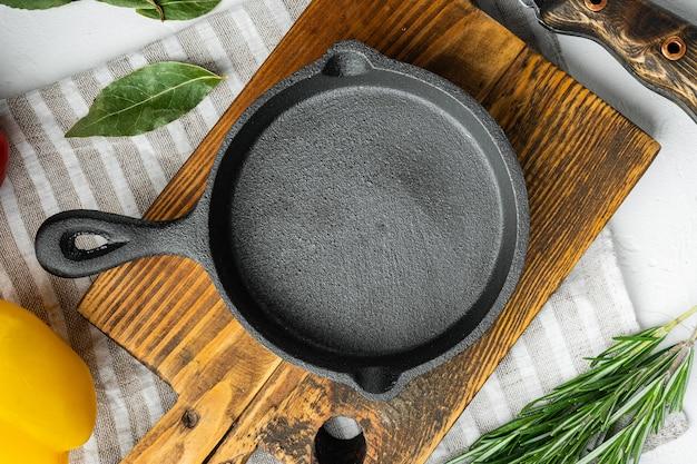 Pusty stół do smażenia z żeliwnej patelni, zestaw koncepcji gotowania naczyń kuchennych, na białej kamiennej powierzchni, widok z góry na płasko