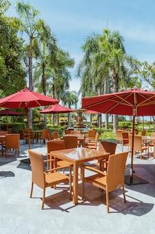 Pusty stół i krzesło na zewnątrz patio z parasolem