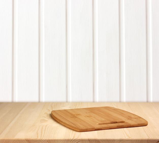 Pusty stół przy białej drewnianej ścianie.
