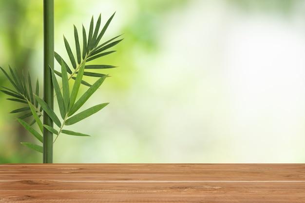 Pusty stół z drewna i bambusa pozostawić na tle przyrody bokeh.