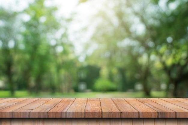 Pusty stół z drewna i niewyraźne bokeh i rozmycie tła drzew ogrodowych światłem słonecznym. szablon wyświetlania produktu.