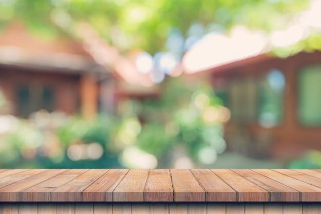 Pusty stół z drewna i niewyraźne bokeh i rozmycie tła drzew ogrodowych światłem słonecznym. wyświetlacz produktu
