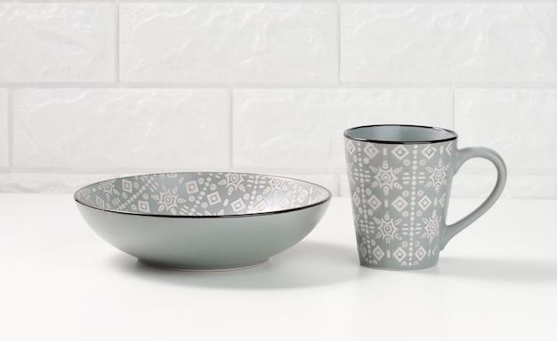 Pusty szary ceramiczny talerz do zupy i pusty kubek na białym stole, naczynia