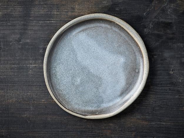 Pusty szary talerz ceramiczny na ciemnym drewnianym stole kuchennym, widok z góry