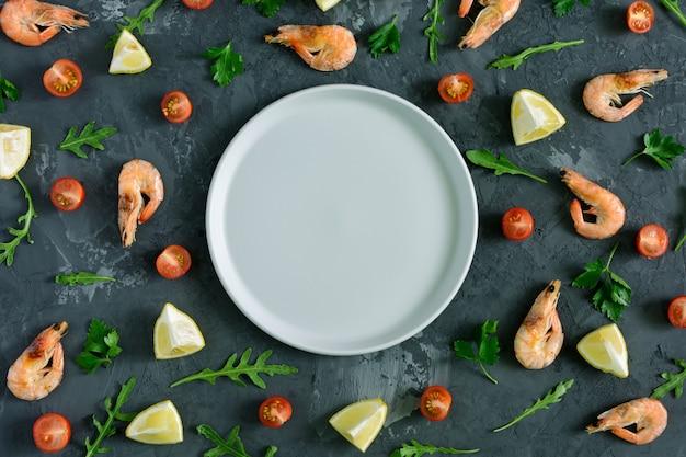 Pusty szary talerz leży pośrodku ciemnego, teksturowanego tła. wokół rozrzucona jest cytryna, natka pietruszki, rukola, pomidory koktajlowe i krewetki. zdjęcia z góry, makiety.