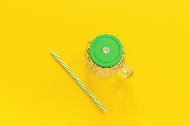 Pusty szklany słoik w formie ananasa z zieloną pokrywką i słomką do koktajli owocowych lub warzywnych, koktajli na żółtym tle.