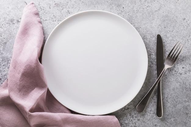 Pusty talerz ceramiczny biała serwetka i sztućce na widoku z góry stołu