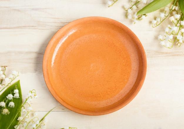 Pusty talerz ceramiczny na drewniane tła. bukiet kwiatów konwalii. skopiuj miejsce.