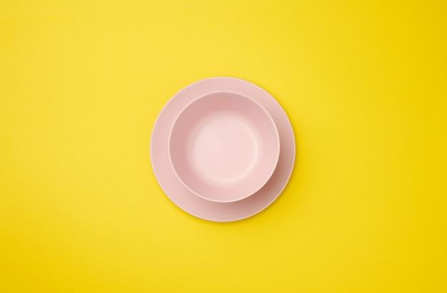 Pusty talerz ceramiczny na żółtym tle, widok z góry
