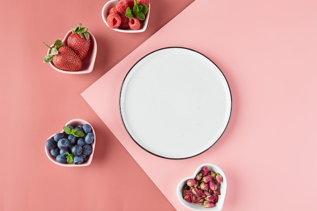 Pusty talerz i małe talerzyki w formie serc ze świeżymi truskawkami, malinami, jagodami, widok z góry