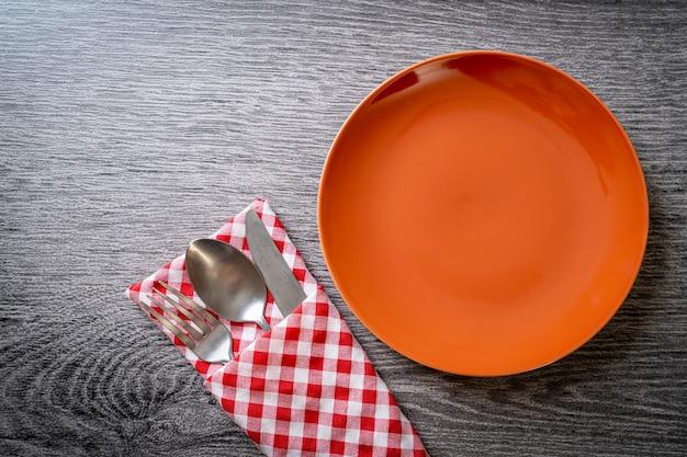 Pusty talerz lub danie z nożem, widelcem i łyżką na stole z drewnianych płytek