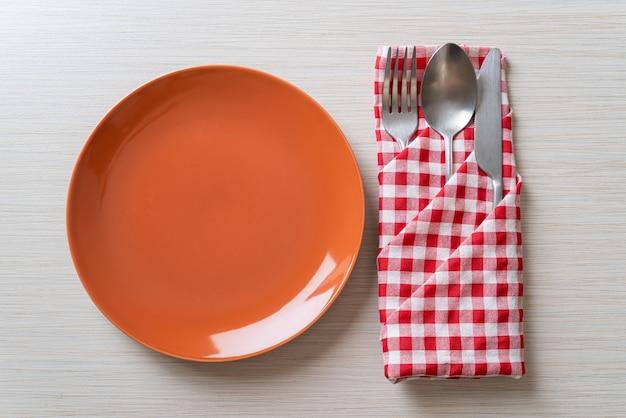 Pusty talerz lub danie z nożem, widelcem i łyżką na tle płytki drewna