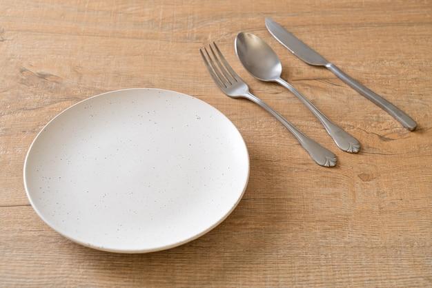Pusty talerz lub naczynie z nożem, widelcem i łyżką na drewnianej płytce