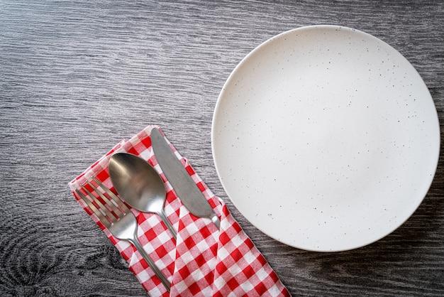 Pusty talerz lub naczynie z nożem, widelcem i łyżką na drewnianym stole