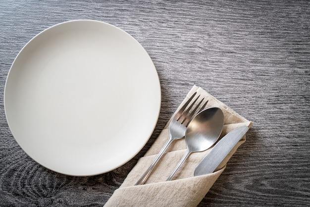 Pusty talerz lub naczynie z nożem, widelcem i łyżką na tle płytki drewna
