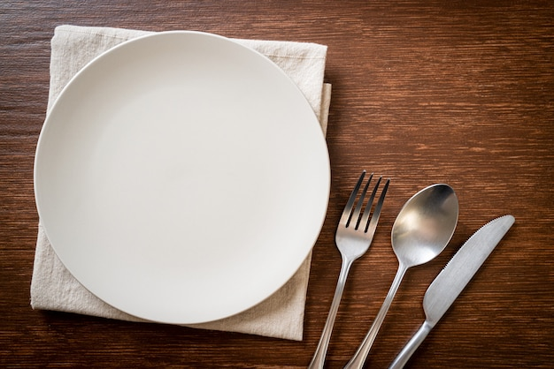 Pusty talerz lub naczynie z nożem, widelcem i łyżką
