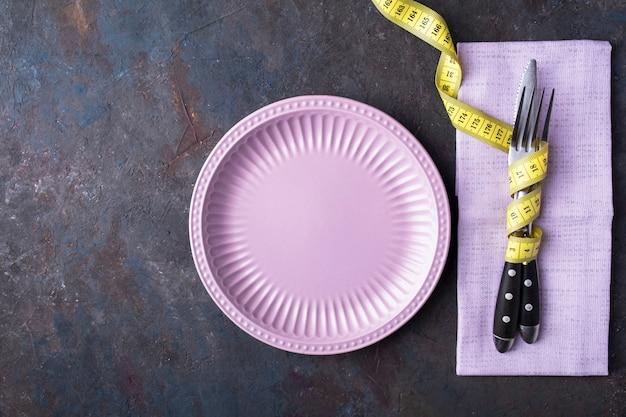Pusty talerz, nóż i widelec za pomocą taśmy mierniczej. pojęcie diety żywności. widok z góry.