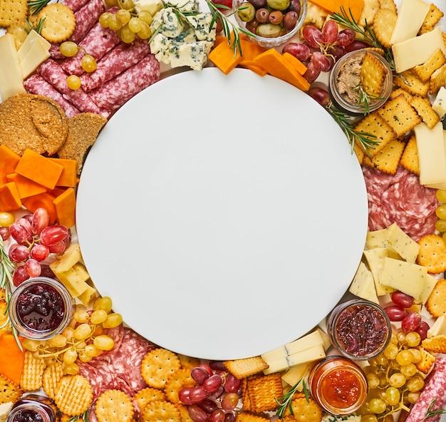 Pusty talerz otoczony różnymi serami, salami, krakersami