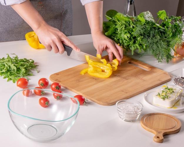 Pusty talerz, pieprz, pomidory, warzywa, sól, składniki do sałatki. kobieca ręka tnie pieprz na drewnianej desce na kuchennym stole. gotowanie krok po kroku