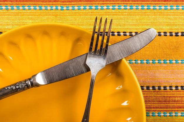 Pusty talerz porcelanowy i widelec na tle obrusu
