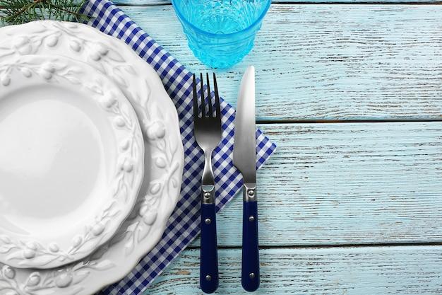 Pusty talerz, sztućce, serwetka i szkło na rustykalnym drewnianym stole. koncepcja nakrycia stołu bożonarodzeniowego