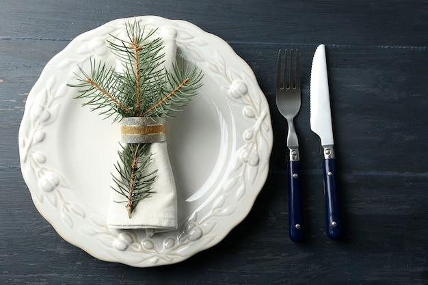 Pusty talerz, sztućce, serwetka na rustykalnym drewnianym stole. koncepcja nakrycia stołu bożego narodzenia