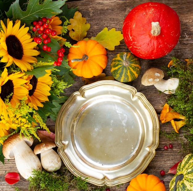 Pusty talerz wieku z pieczarkami, mchem, liśćmi i ramą dyni na drewnianym stole, przygotowanie obiadu na święto dziękczynienia
