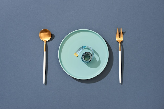 Pusty talerz z miarką, nożem i widelcem. dietetyczne jedzenie na tabeli kolorów