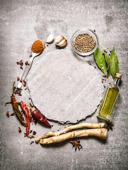 Pusty talerz z pikantnymi przyprawami i ziołami dookoła. na kamiennym stole. wolne miejsce na tekst. widok z góry