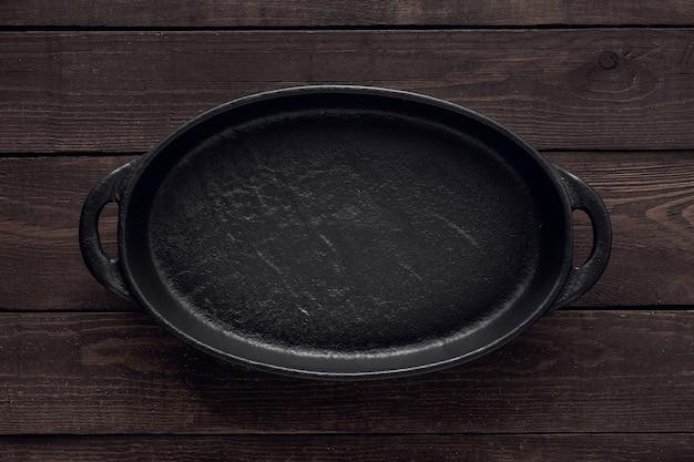 Pusty talerz żeliwny do serwowania potraw na tle drewnianych, widok z góry.