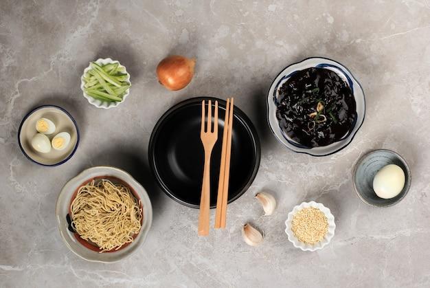 Pusty ttukbaegi flat lay concept składniki jajangmyeon lub jjajangmyeon, koreański makaron z sosem z czarnej fasoli. na szarym cementowym drewnianym tle