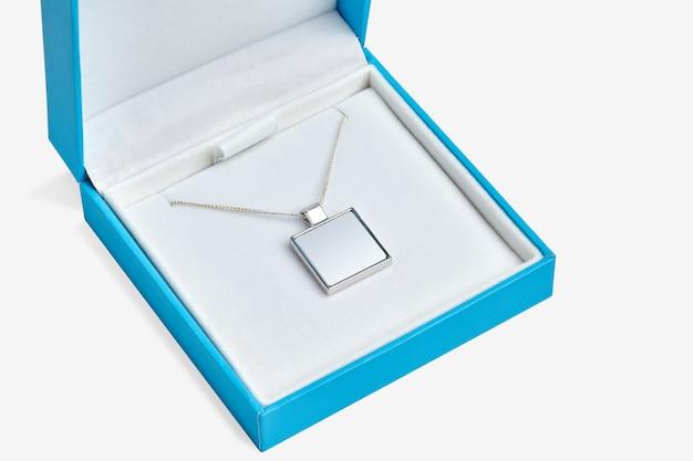 Pusty wisiorek na łańcuszku lub medalionie w niebieskim pudełku z biżuterią