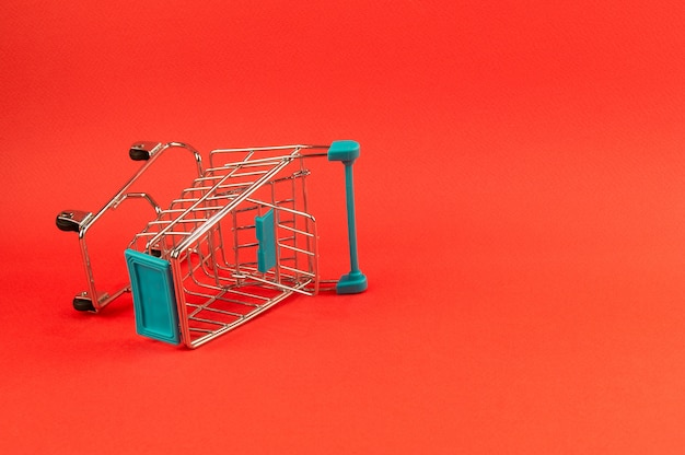 Pusty wózek na zakupy na jaskrawym czerwonym tle