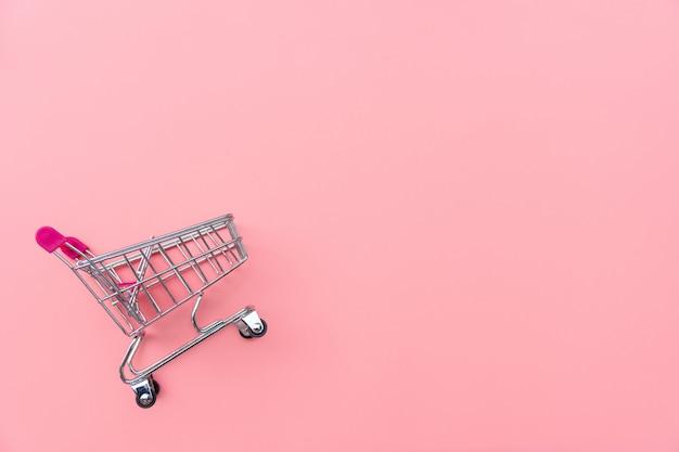 Pusty wózek na zakupy na różowym tle. zakupy, zakupy online pojęcie., kopii przestrzeń, odgórny widok