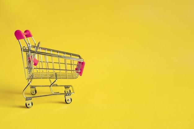 Pusty wózek na zakupy z różowym uchwytem na żółto. zakupy online . forma handlu elektronicznego.