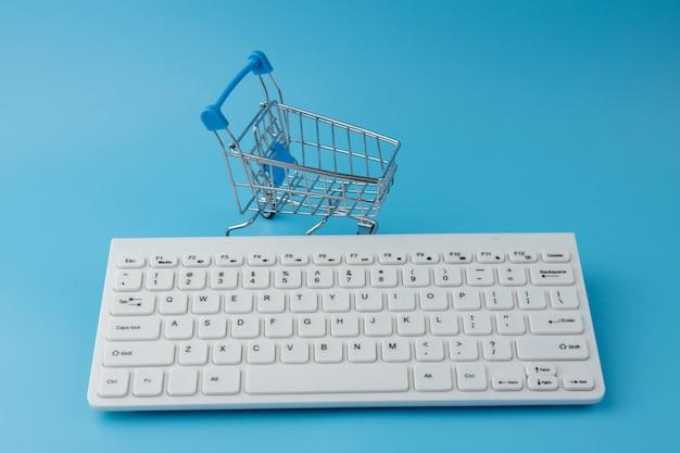 Pusty wózek spożywczy z klawiaturą. zakupy online, koncepcja zakupów internetowych