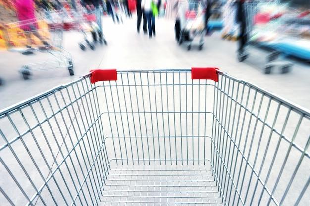 Pusty wózek w supermarkecie lub centrum handlowym pełnym zatłoczonych ludzi. rozmycie ruchu.