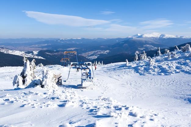 Pusty wyciąg narciarski pokryty szronem i śniegiem z górami w tle
