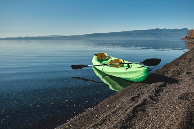 Pusty zielony kajak bez ludzi z wiosłami na skraju plaży. na tle błękitnego nieba i wody