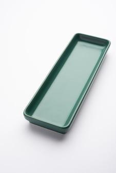 Pusty zielony prostokątny talerz ceramiczny na białym tle