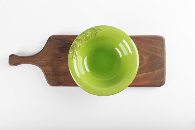 Pusty zielony spodek na białym stole na drewnianej desce