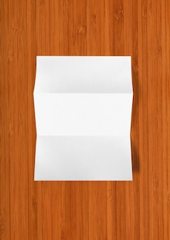 Pusty złożony arkusz papieru a4 na białym tle na ciemnej powierzchni drewnianych