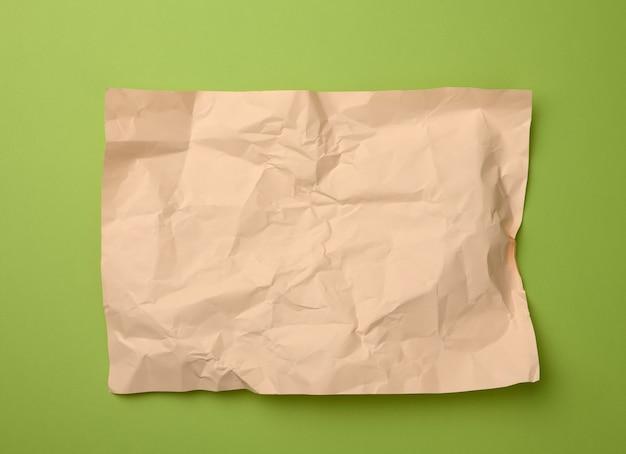 Pusty zmięty arkusz papieru beżowy na zielonej powierzchni, kopia przestrzeń. format a4