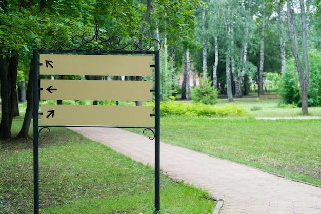 Pusty znak w parku przy ścieżce na tle drzew