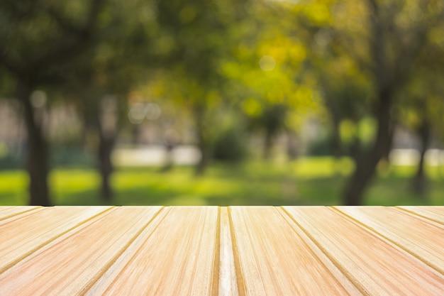 Pusty żółty drewniany stół z zamazanym miasto parkiem