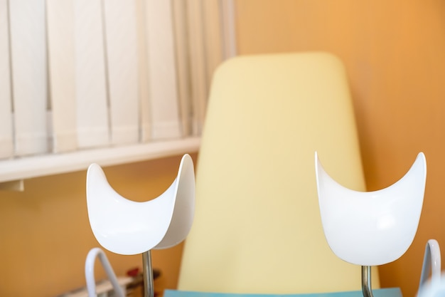 Pusty żółty fotel ginekologiczny w nowoczesnym centrum medycznym. koncepcja zdrowia kobiet